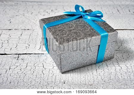 Gift birthday Christmas present concept - silver gift box with blue ribbon on white painted wooden background