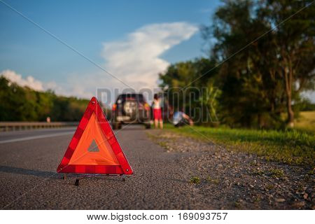 Close-up Of A Triangular Warning Sign With Couple Standing In Front Of Broken Down Car shallow depth of field, the focus is on the triangle
