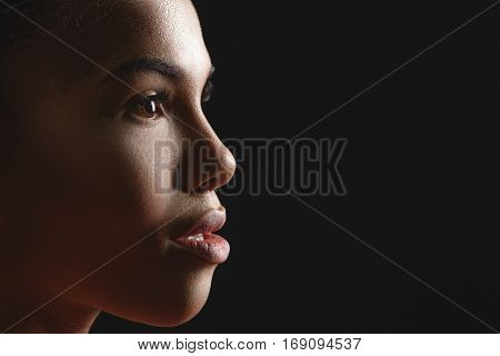 Close up of beautiful female face in profile. Mulatto woman is looking straight with confidence. Isolated on black background. Copy space in right side
