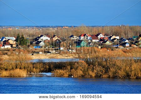 Spring rural landscape - small village in early spring at sunset birds eye view. Spring background, colorful spring landscape view. Vollage in spring time