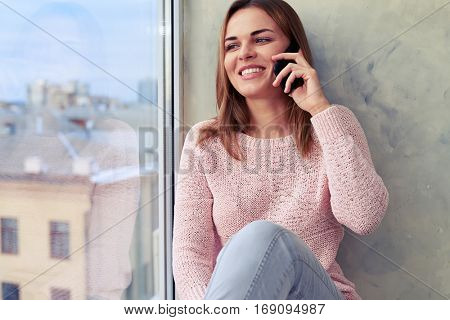 Close-up side shot of happy woman using telephone. Sitting on the windowsill. Have a rather lively conversation