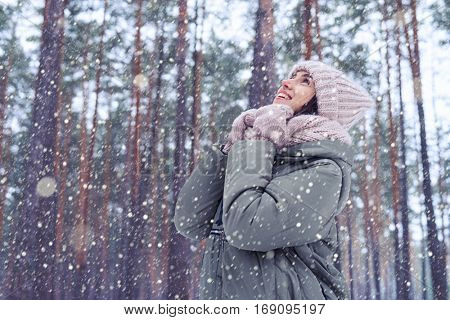 Low angle of thoughtful attractive trendy woman in stylish winter fashion clothes making a wish. Everything seems quieter, almost muffled. Looking upwards