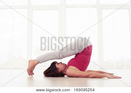 Side view of sporty Caucasian woman lying on back with arms at sides, palms down. Practicing halasana plow pose on the mat in the gym