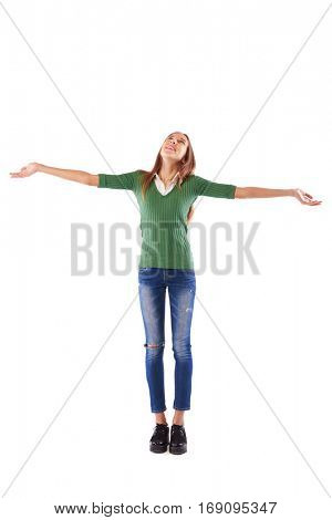 Full-length portrait of girl who is spreading hands and looking up on the copy space while standing in studio over white background