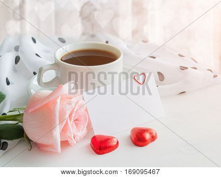 St Valentines day background - cup of coffee rose blank love card in pastel tones. St Valentines day still life with card for St Valentines daymessage. St Valentines day background