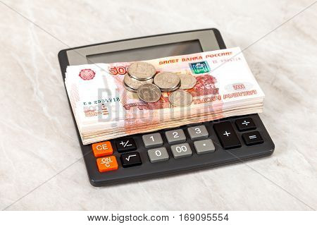 Stack of five thousandths banknotes of russian roubles coins and calculator