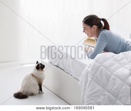 Lovely birman cat and its owner relaxing in the bedroom the woman is lying on the bed and the cat is looking at her