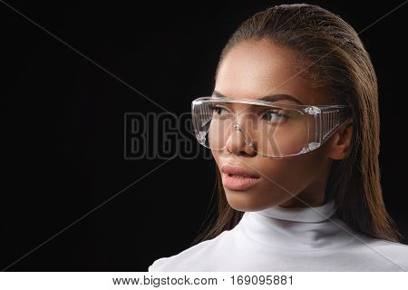 Curious young african woman is observing something. She is wearing big eyeglasses and white pullover. Isolated. Copy space in left side