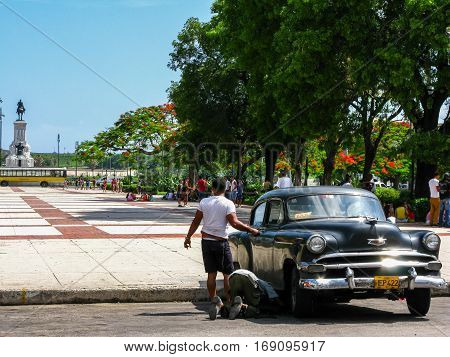 Two men repairing vintage Chevy in Havana center, Cuba, on June 4, 2009.