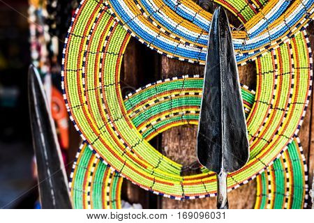 Masai colorful decorations and spear at local african souvenir market