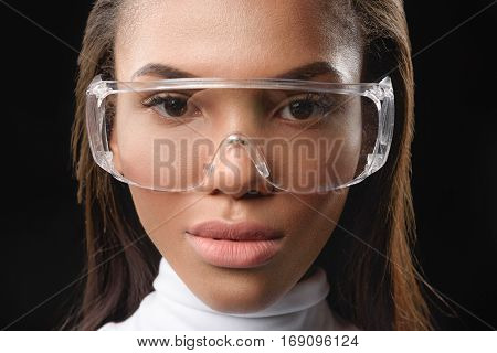 Close up of face of young mulatto girl in modern wide glasses. She is looking at camera with confidence