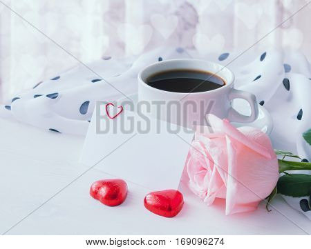 Love background - cup of coffee rose blank love card and heart shaped candies cold pastel tones applied. Lova still life with love blank card for love message