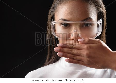 No talk. Serious young mulatto girl is covering her mouth by hand. She is looking at camera confidently. Isolated and copy space in left side