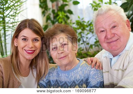 Picture of a senior couple with their cheerful caregiver at home
