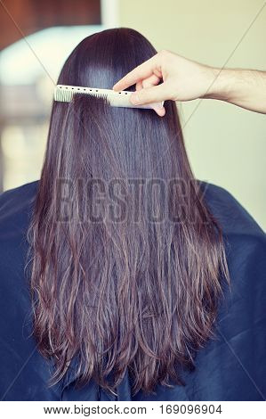 beauty, hair care, hairstyle and people concept - stylist hand with comb combing woman hair at salon
