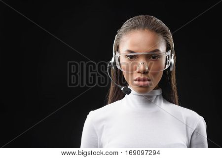 Clever female receptionist is speaking into microphone on headset. Woman is looking forward with confidence. Isolated and copy space in left side