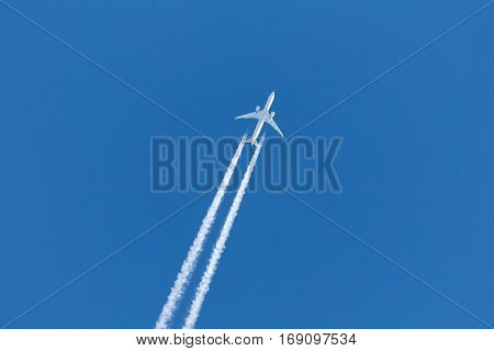 jet plane leaves contrail in a clear blue sky closeup