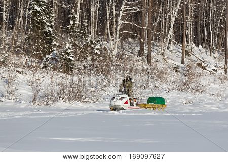 man on a snowmobile carrying barrels of fuel