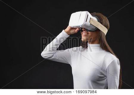 Excited young mulatto girl is using vr headset and smiling. Isolated and copy space in left side