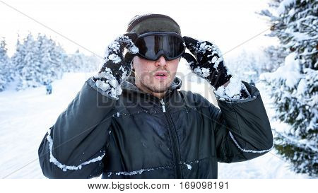 Snowboarder standing on a ski in winter and keeps his hands a ski mask closeup portrait