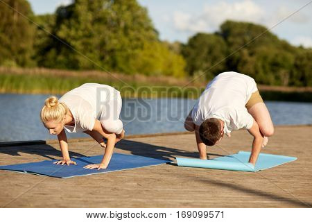 fitness, sport, yoga, people and healthy lifestyle concept - couple making side crow pose on mat on river or lake berth