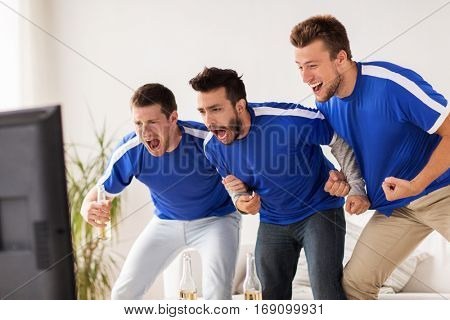friendship, sport, people and entertainment concept - happy male friends or football fans watching soccer on tv at home