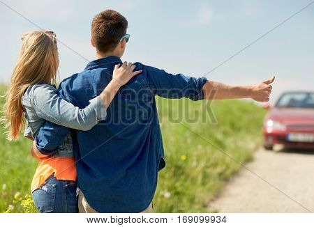 road trip, hitchhike, travel, gesture and people concept - happy couple hitchhiking and stopping car at countryside