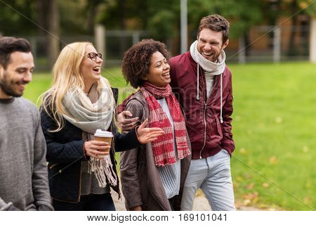 people, friendship, communication and international concept - group of happy friends with coffee walking along autumn park and laughing
