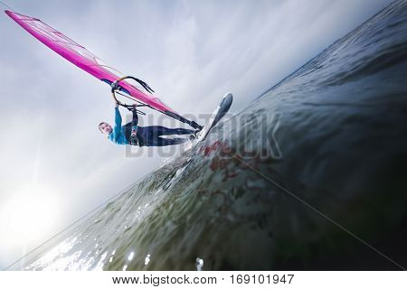windsurfer with speed on a big lake gliding towards the camera with sunset in the background