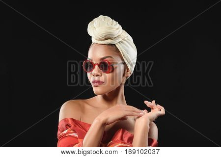 Calm young african woman is posing with elegance. She is wearing turban and sunglasses. Isolated on black background