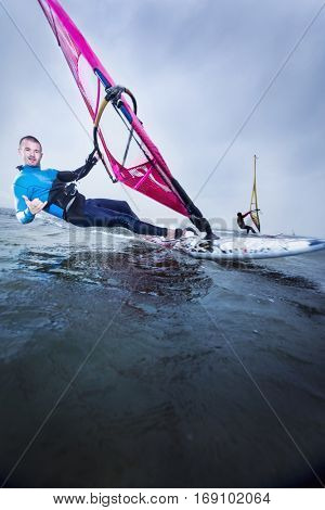 windsurfer at speed with a smile and a greeting sign