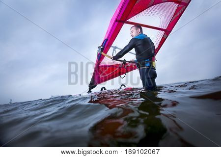 professional windsurfer waiting for the right wind in the middle of a big lake