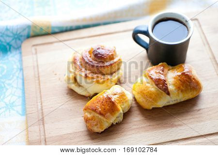 Breakfast still life: coffee cup with rolls, bun, home made croissant. Cutting board background. up view soft focus photo
