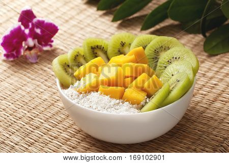 Fruit smoothie with mango kiwi fruit in a bowl on a straw background