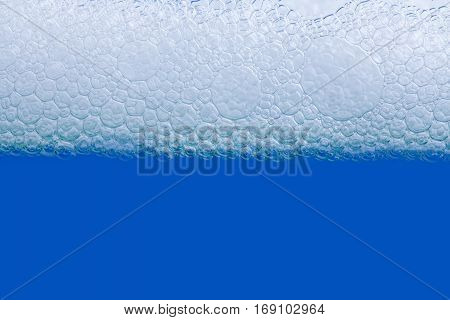 Soap bath bubbles macro view. Laundry detergent, suds textured pattern. White soapsuds on blue background, copy text, horizontal