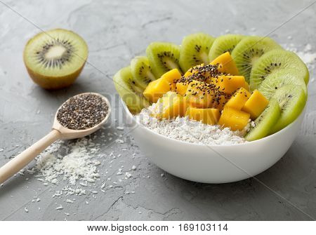 Banana smoothie with mango kiwi chia seeds in a bowl on a gray concrete background