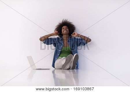 Portrait of happy young african american woman sitting on floor with laptop