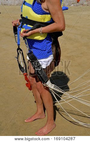 A young lady standing on the beach sand is strapped and ready for parasailing