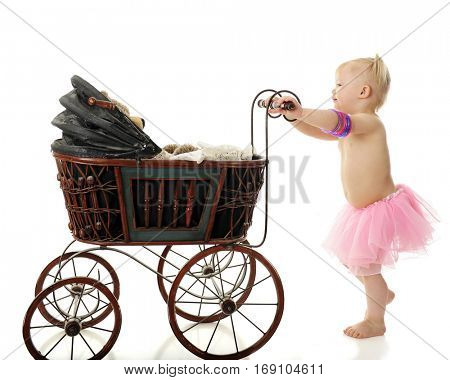 An adorable 2-year-old wearing a pink tutu and bangles giving her toy bear a ride in an antique doll buggy.  On a white background.