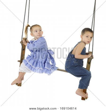 Two preschool kids swinging on an antique, wooden pump swing.  The girl is looking over her shoulder at the top of the swing while the boy looks a bit worried at the viewer.  On a white background.