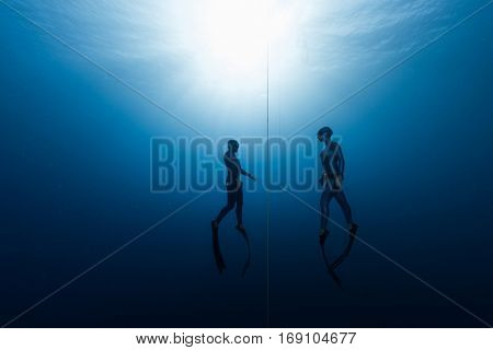 Two free divers, man and woman, ascending from the depth along the rope