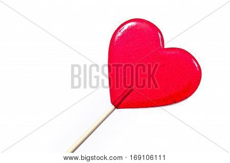 Gift for Valentines day. Red lollipop in the shape of a heart on the white background.
