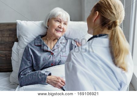 Friendly female physician looking after her old patient. Smiling elderly woman listening doctor while lying on bed