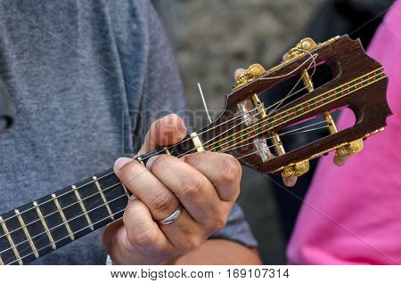 Small guitar with four strings called cavaquinho in Brazil and traditionally used in the styles of samba and chorinho