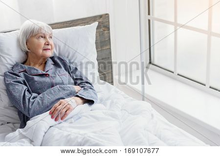 Old inpatient woman is on drop glass watching at wide window, lying on white bed in hospital