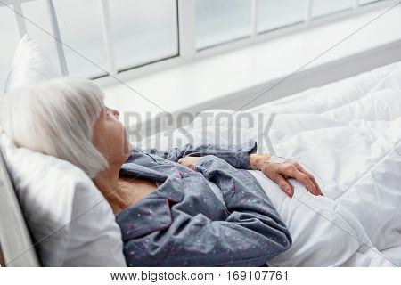 Calm grandmother reclining on bed while looking at window in room of clinic