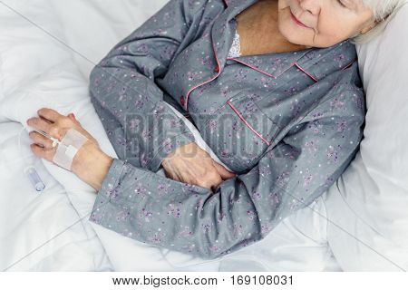 Serene old woman is on drip flask while she sleeping on soft bed in polyclinic