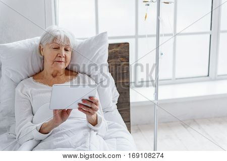 Calm senior looking at digital tablet while keeping it in hand and lying on bed in hospital