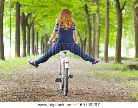Young woman riding a bike at the park with her legs in the air