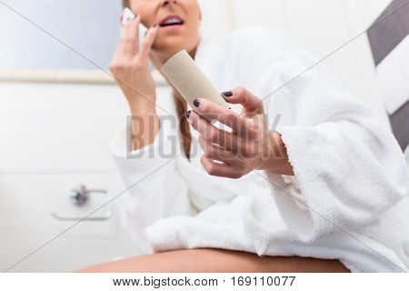 Woman in bathroom sitting on toilet and complaining via phone about lack of paper